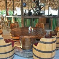 The restaurant is situated in an outdoors environment and is quite casual and very authentic in appearance, containing wooden tables, barrel stools and grass-like thatch umbrellas on the sea side.